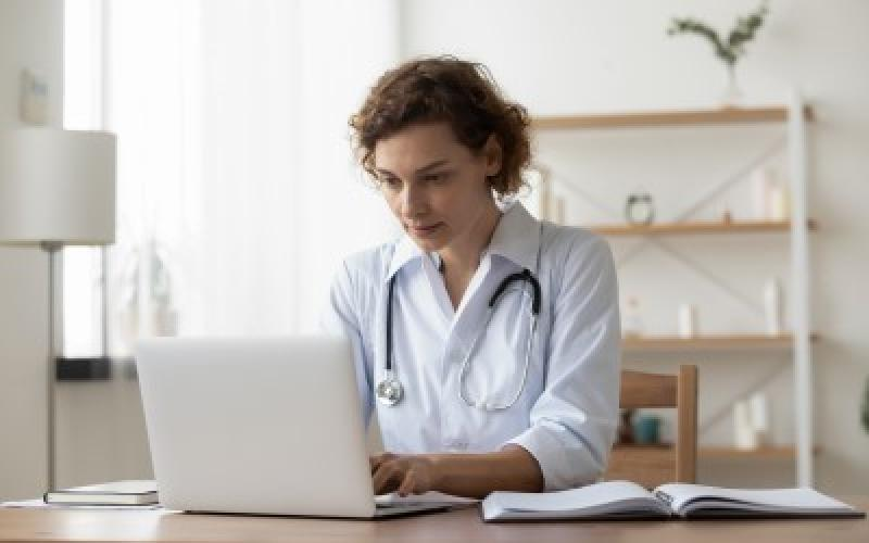Pfizer-science-medical_information_queries-female_doctor_with_stethoscope_working_on_laptop